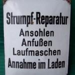 Altes Reklameschild für Strumpfreparaturen.
